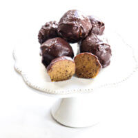 A decorative grey platter stacked with The BEST Vegan No-Bake Pumpkin Truffles on a solid white background