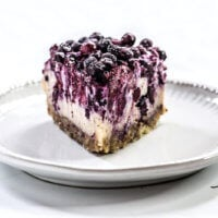 Head-on image of a single slice of Gluten-Free Vegan No-Bake Wild Blueberry Cheesecake on a small grey saucer on a white background