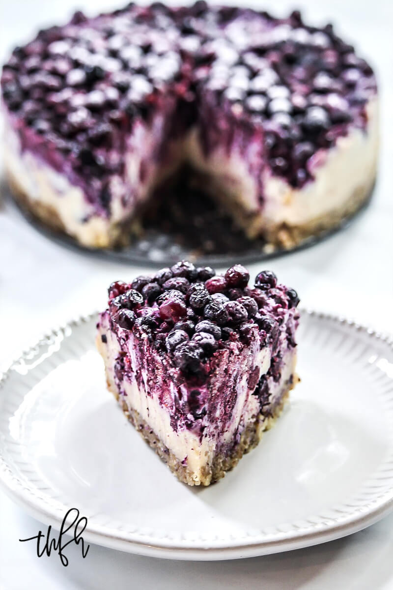 Vertical image of a single slice of Gluten-Free Vegan No-Bake Wild Blueberry Cheesecake on a small grey plate with the entire cheesecake in the background