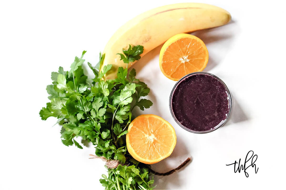 Small glass of dark purple smoothie surrounded by various fruits and veggies on a white background