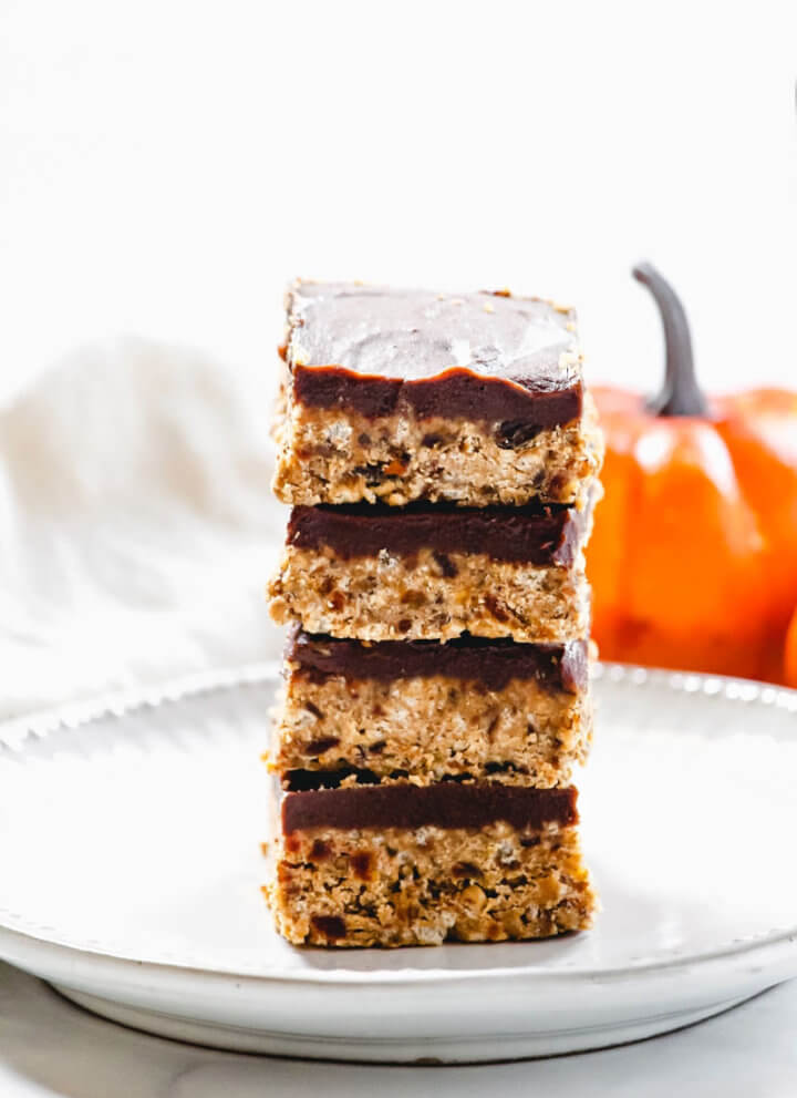 A stack of four Gluten-Free Vegan No-Bake Crispy Pumpkin Spice Squares in the center of a white plate with a small pumpkin in the background
