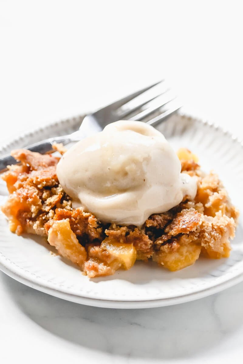 Vertical image of a grey plate filled with peach cobbler with a scoop of vanilla ice cream on top on a solid white surface