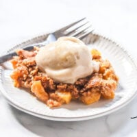 A small grey plate with a serving of Gluten-Free Vegan Flourless Peach Cobbler with a scoop of vanilla ice cream on top and a silver spoon to the side