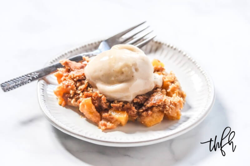 A small grey plate with a serving of Gluten-Free Vegan Flourless Peach Cobbler in the center with a scoop of vanilla ice cream on top and a silver fork to the side
