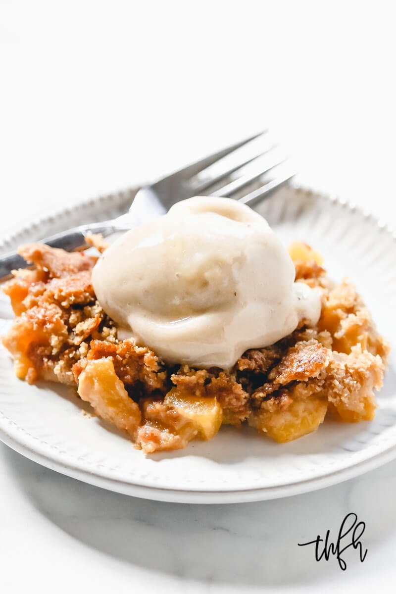 Vertical image of a grey plate with a serving of peach cobbler with a scoop of vanilla ice cream on top on a white marbled surface