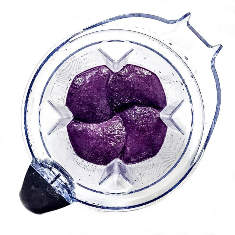Overhead image of a purple blended smoothie inside a Vitamix blender