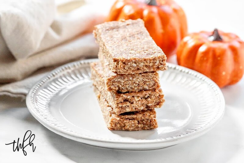Horizontal image of a stack of four Gluten-Free Vegan No-Bake Pumpkin Spice Granola Bars on a decorative grey plate with two small pumpkins in the background