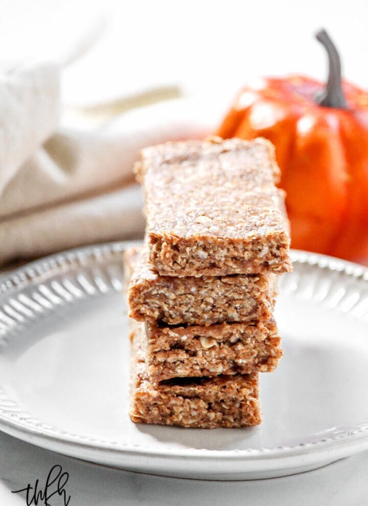 Vertical image of a stack of four Gluten-Free Vegan No-Bake Pumpkin Spice Granola Bars on a small grey plate with a cloth napkin and small pumpkins in the background