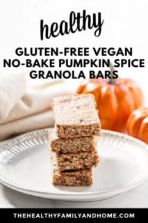 A stack of four Gluten-Free Vegan No-Bake Pumpkin Spice Granola Bars on a decorative plate with two pumpkins in the background and text overlay