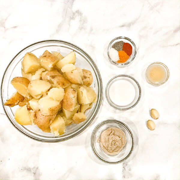 Image of all the ingredients needed to make Gluten-Free Vegan Turmeric and Black Pepper Mashed Potatoes measured out in glass bowls on a white marbled surface