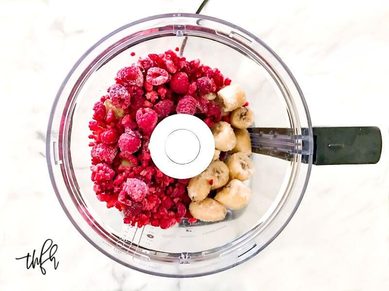 Overhead image of frozen bananas and frozen raspberries in a food processor
