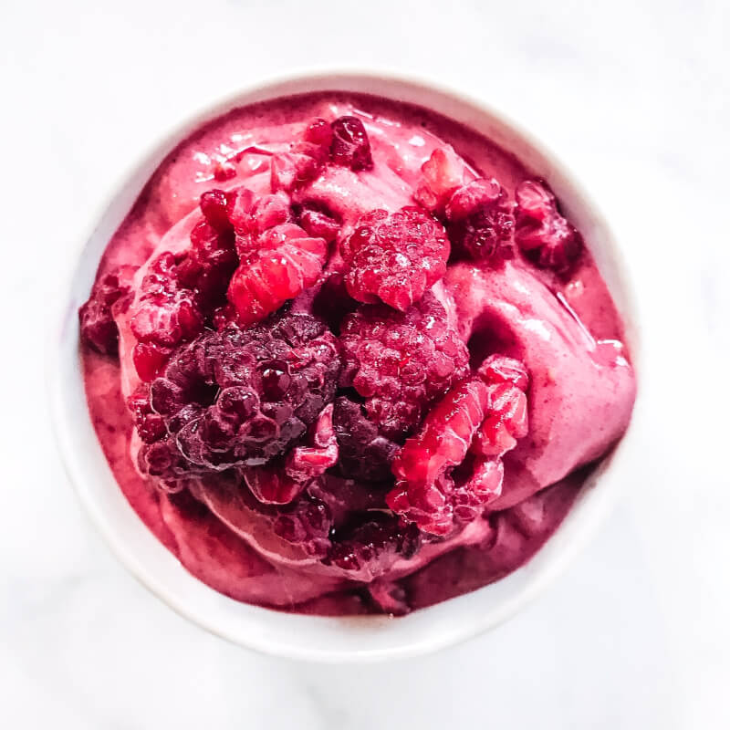 """Overhead image of a white bowl filled with Gluten-Free Vegan Raspberry Banana """"Nice"""" Cream on a white marbled surface"""