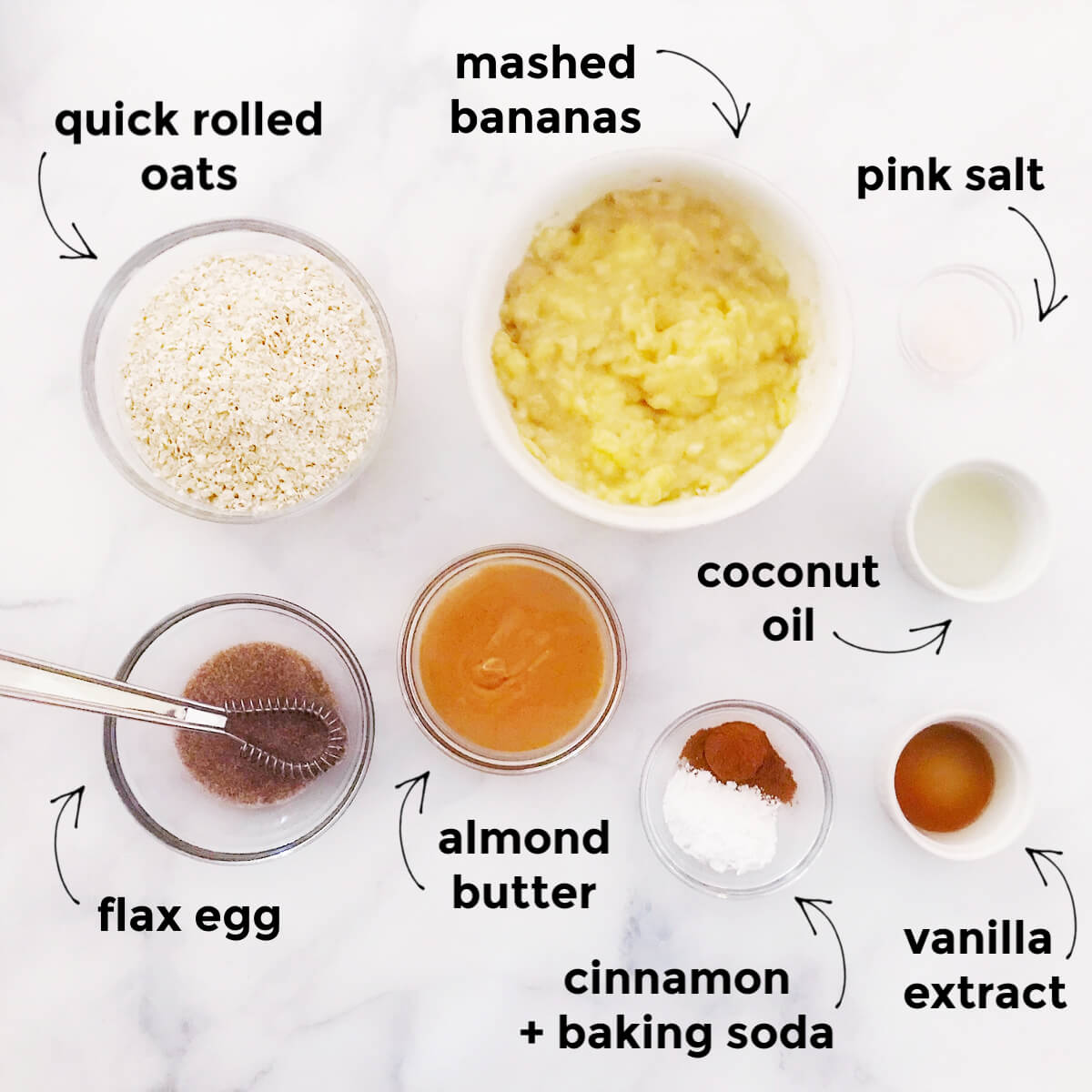 Flat-lay of text labeled ingredients needed to make baked oatmeal breakfast squares on a solid white surface