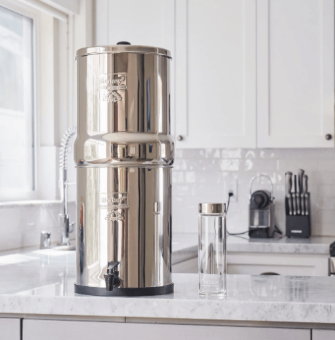 A Berkey water purification unit sitting on top of a white countertop in a clean bright kitchen